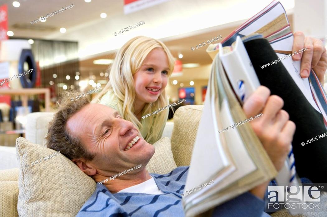 Stock Photo: Man looking at fabric samples in furniture shop with daughter 6-8, low angle view.