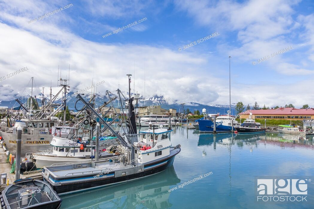 Imagen: Big white clouds with patches of blue sky over small boat harbor on Prince William Sound in Valdez Alaska.