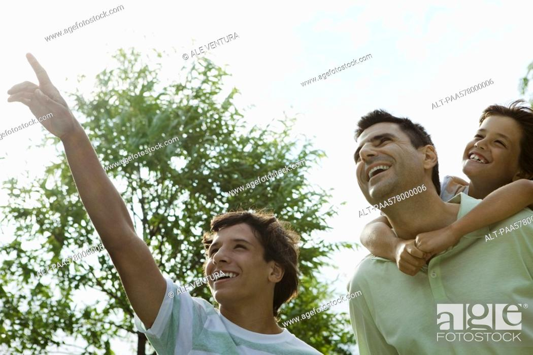Stock Photo: Father and sons exploring together outdoors.