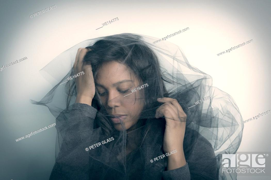 Stock Photo: Young Hispanic woman with a veil covering her head.