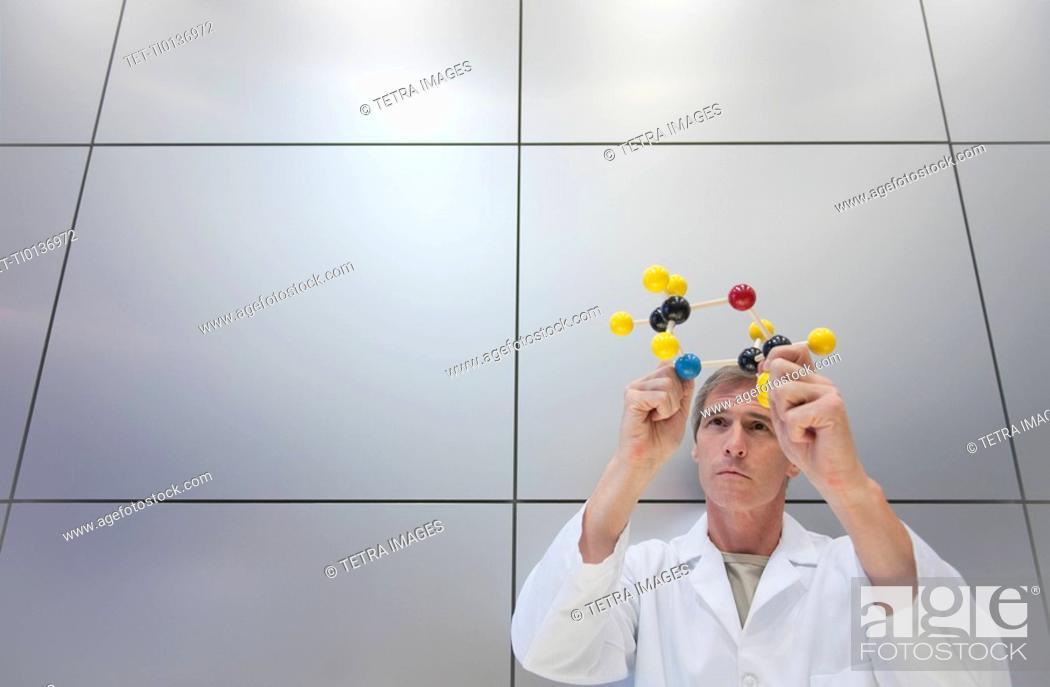 Stock Photo: Reseacher holding molecular model.