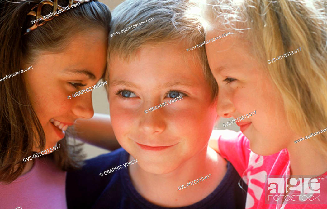 Stock Photo: Close-up of a boy standing between two girls.