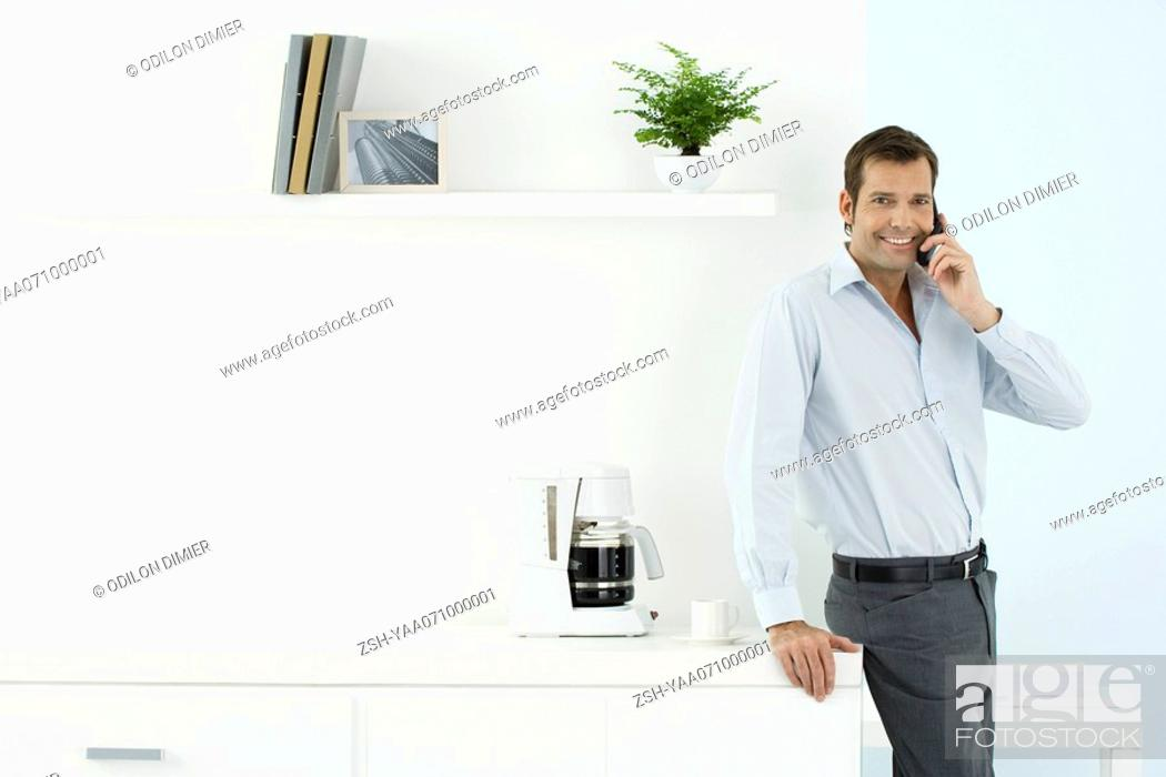 Stock Photo: Man using cell phone, smiling at camera, leaning against counter with coffee maker on it.