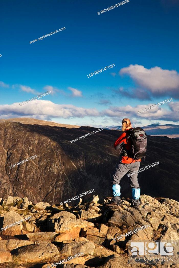 Stock Photo: England, Cumbria, Buttermere. A young woman standing on the sumit of a mountain in the Lake District.