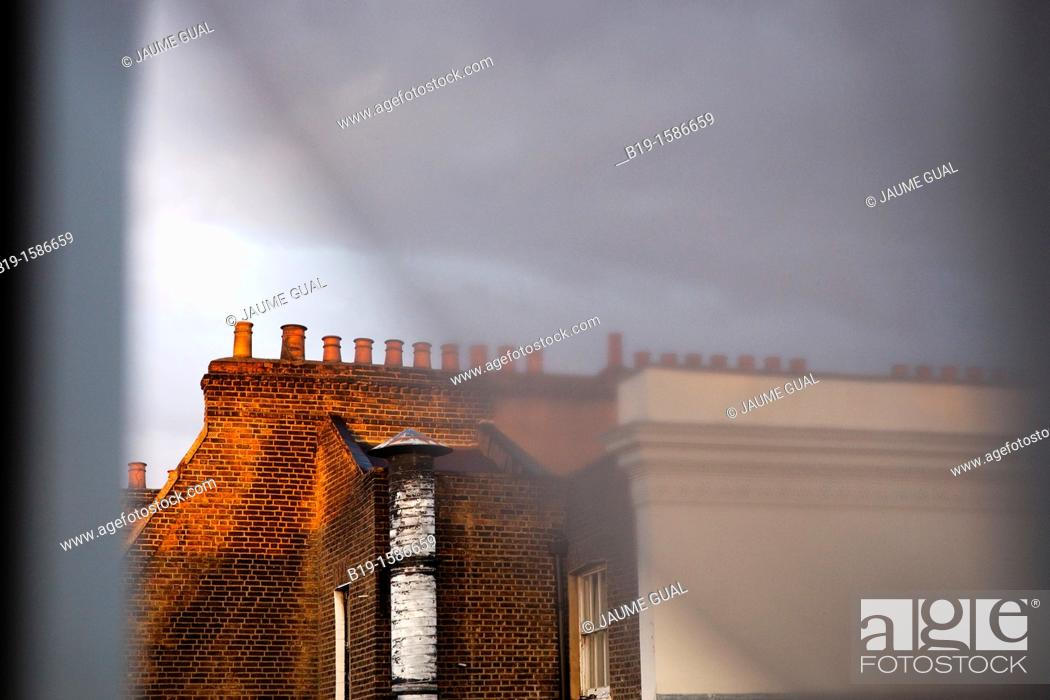 Stock Photo: Chimneys on the top of a London's building through the window and curtains.