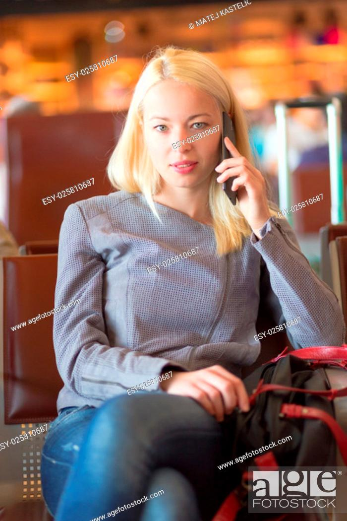 Stock Photo: Casual blond young woman calling by cell phone while waiting to board a plane at the departure gates. Wireless network hotspot enabling people to access.