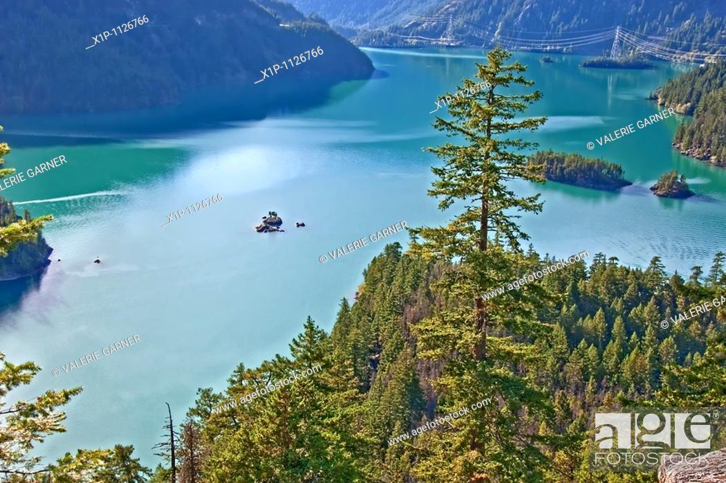 Stock Photo: This landscape stock photo is a beautiful mountain lake with deep rich aquamarine colored water There's also several islands within the lake and evergreen and.