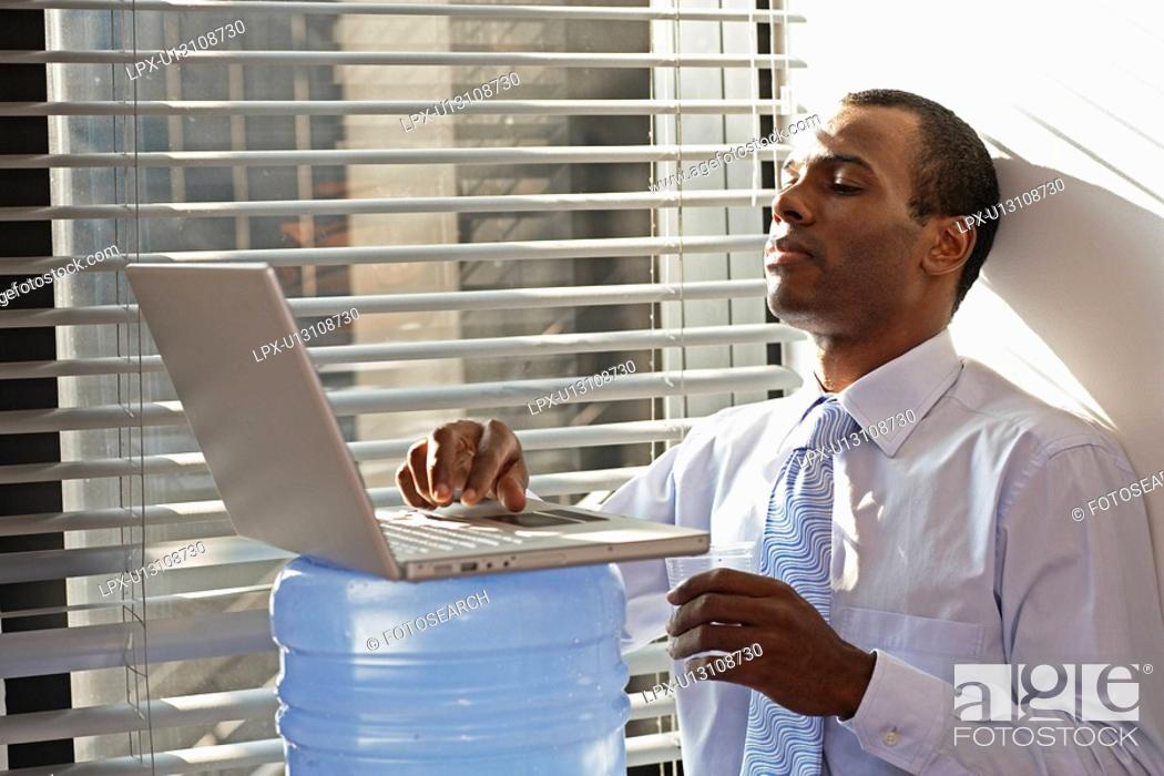 Stock Photo: Mid Adult Man Using Laptop on Water Cooler.