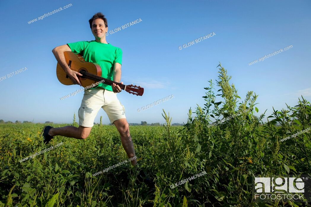 Stock Photo: Man holding a guitar and jumping in a field.