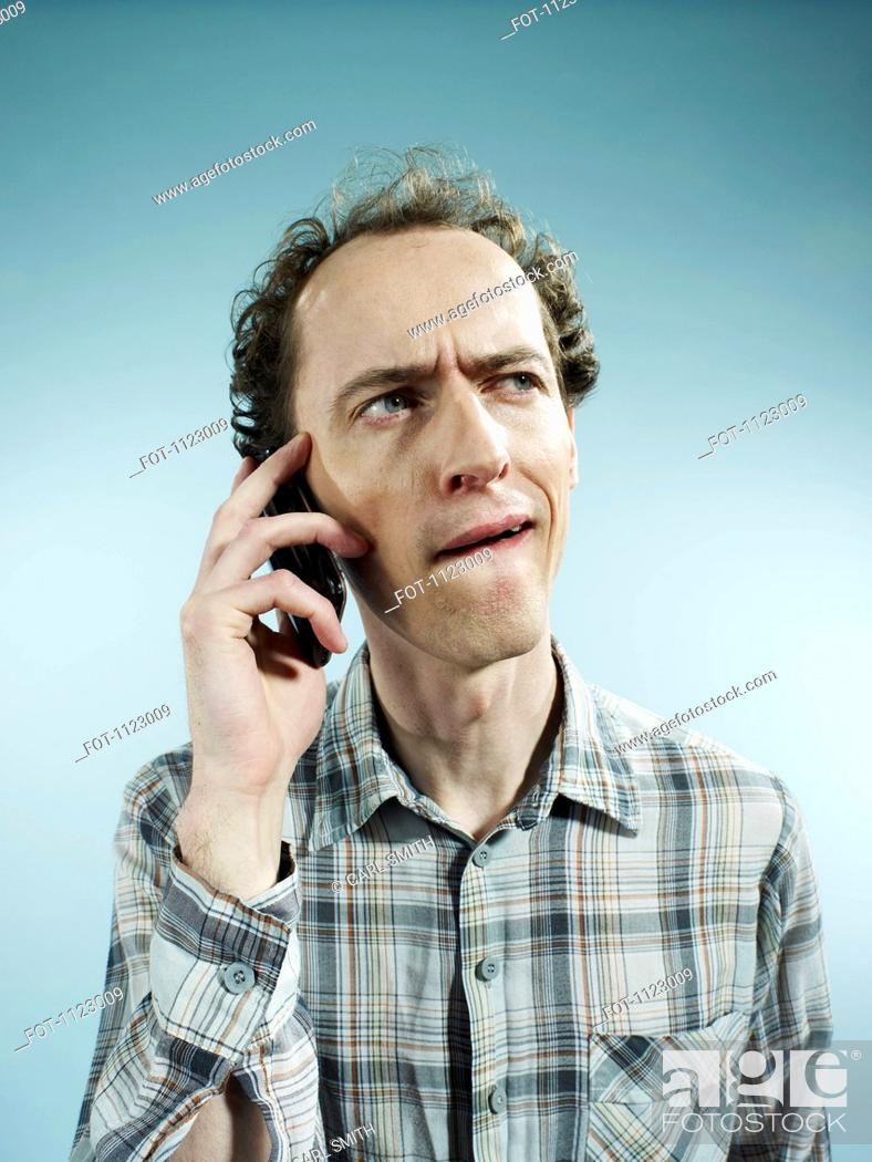 Stock Photo: A man using a mobile phone with a confused look on his face.