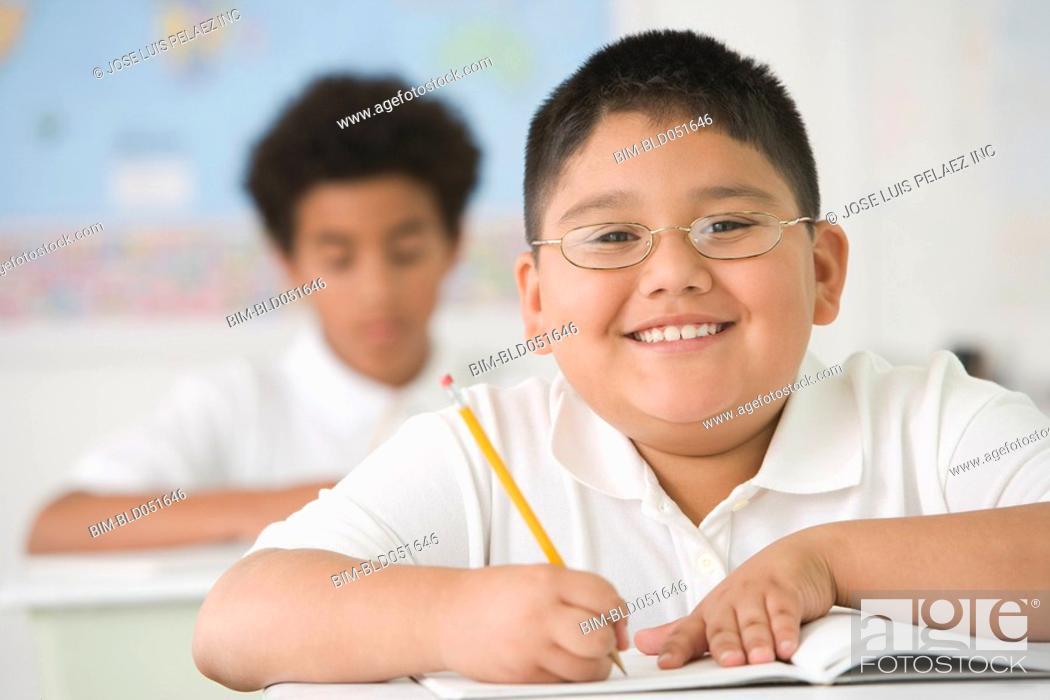 Stock Photo: Hispanic boy writing at school desk.