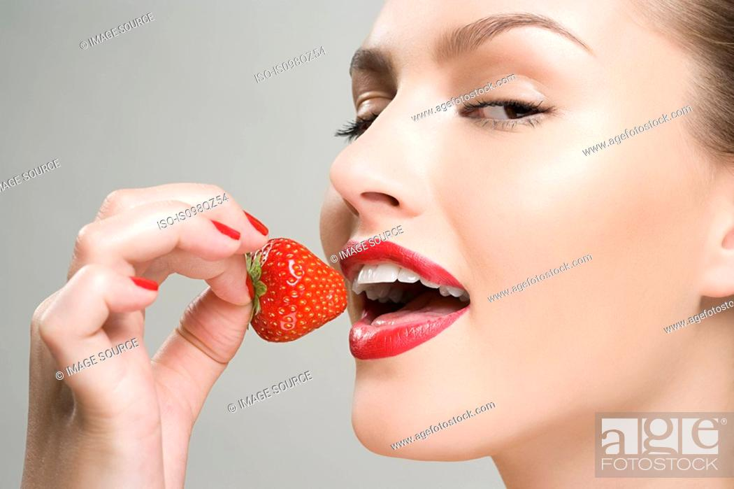 Stock Photo: Woman eating a strawberry.