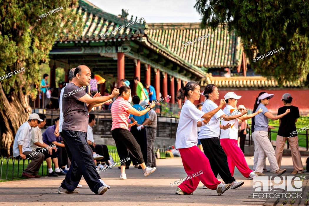 Stock Photo: Chinese people practice tai chi martial arts exercise early morning at the Temple of Heaven Park during summer in Beijing, China.