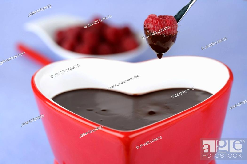 Stock Photo: Heart-shaped chocolate fondue dipping a raspberry.