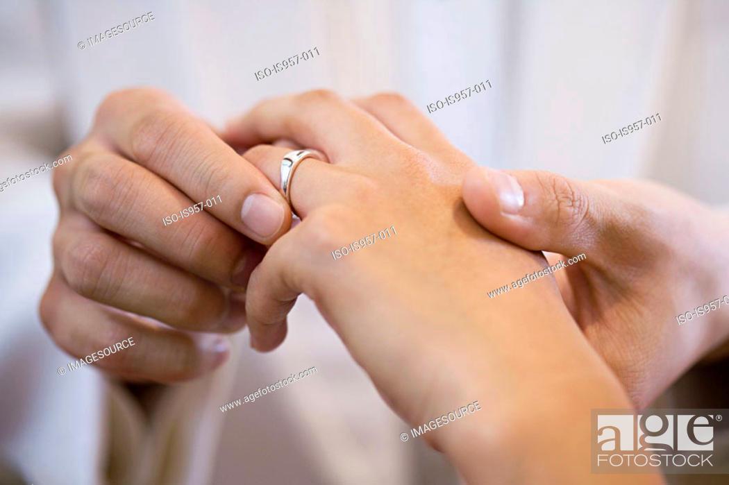 Stock Photo: Groom placing wedding ring on brides finger.