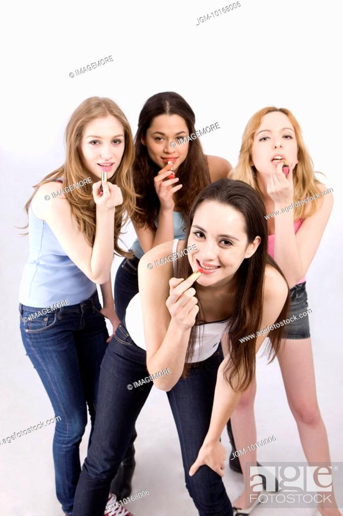 Stock Photo: Four young women applying lipstick.