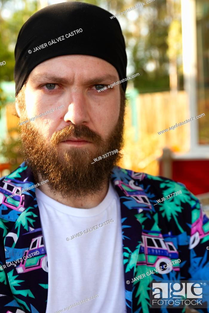 Stock Photo: portrait of serious young man with beard and headscarf.