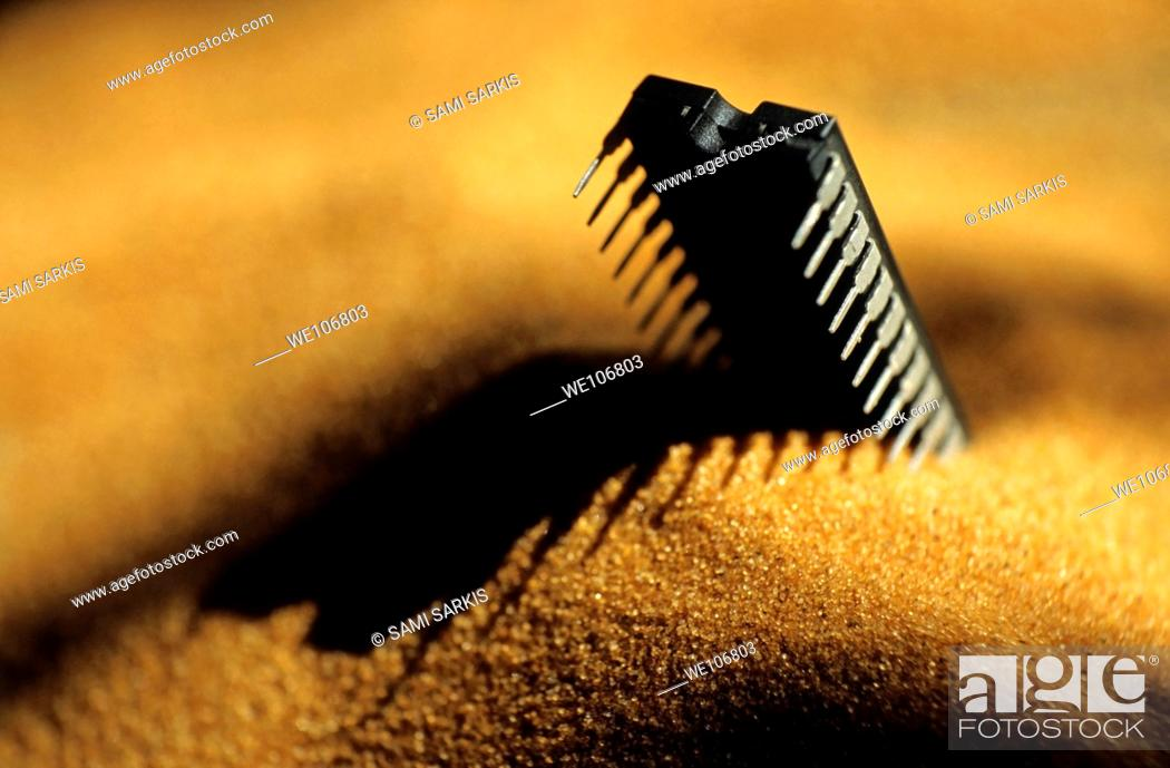 Stock Photo: Computer chip half-buried in sand.