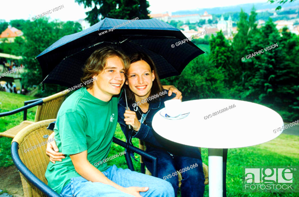 Stock Photo: Young couple sitting together under an umbrella.