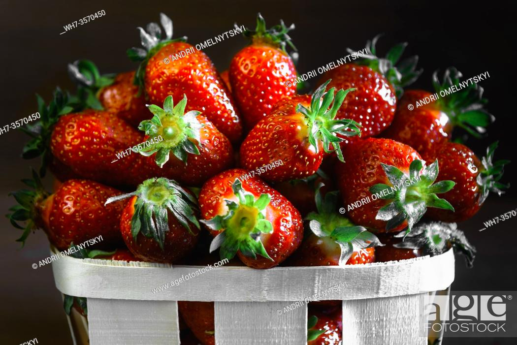 Photo de stock: ripe juicy strawberries on a wooden table in a basket.