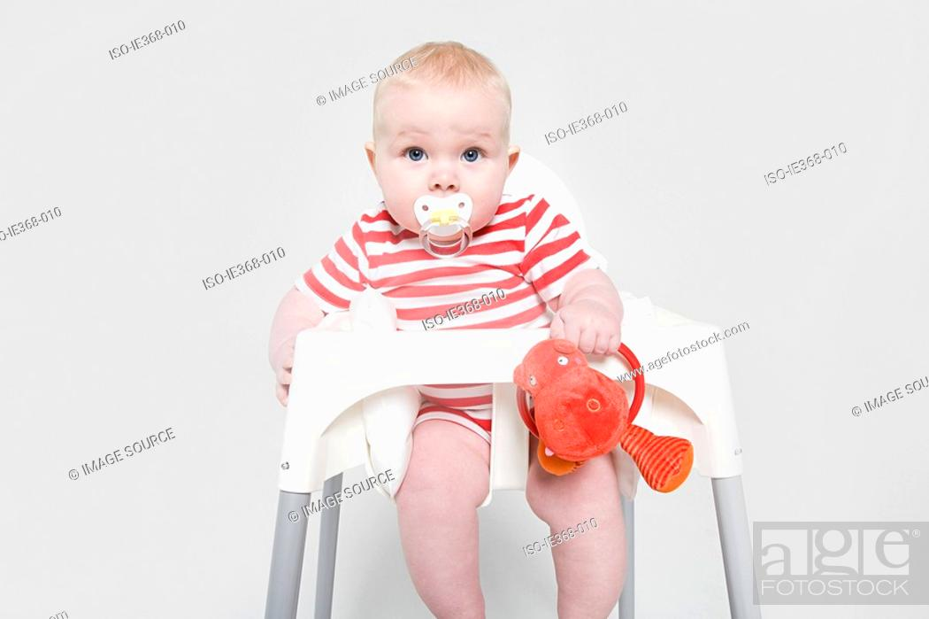 Stock Photo: A baby girl in a high chair.