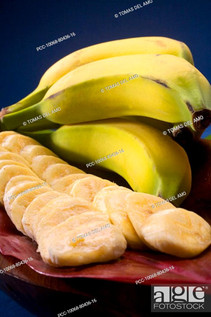 Stock Photo: Studio shot of bananas, whole and cut into slices, with flowers.