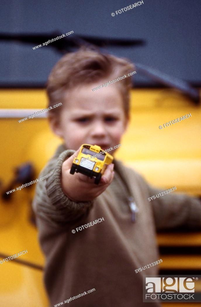 Stock Photo: Young boy playing with toy school bus in front of real bus.