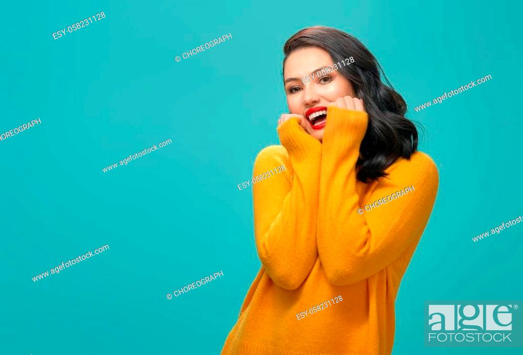Stock Photo: Joyful beautiful young woman in yellow sweater posing on turquoise background.