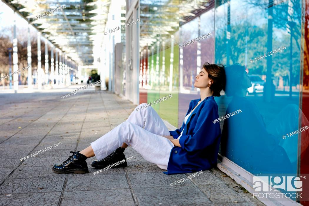 Photo de stock: Young woman with urban look sitting on the floor and leaning on colorful glass wall with her reflection.