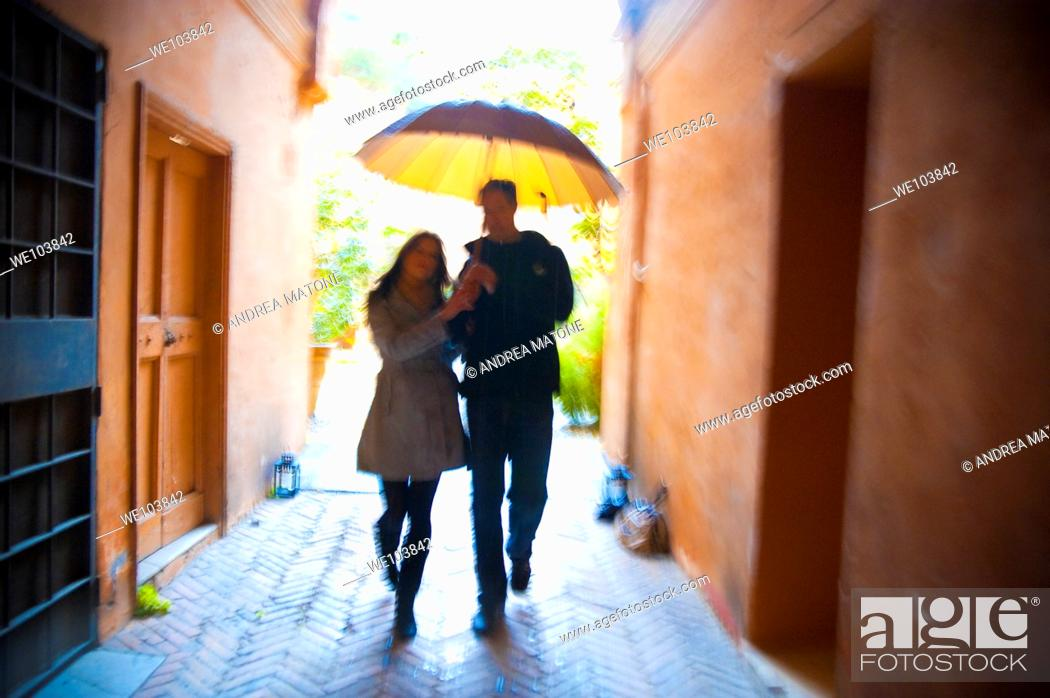 Stock Photo: Couple with motion blur walking together with an umbrella under the rain in Rome Italy.