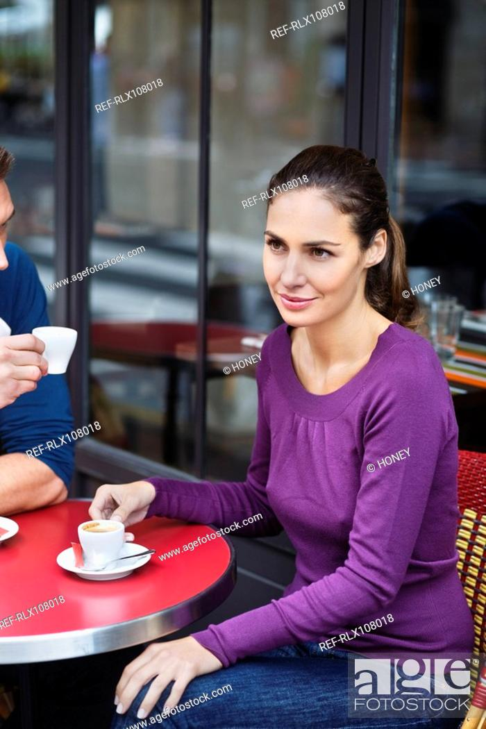 Stock Photo: Young couple sitting at cafe table, outdoors, Paris, France.