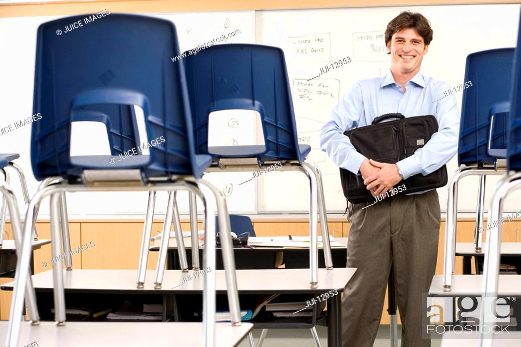Stock Photo: Teacher with bag in classroom by chairs on desks, smiling, portrait.