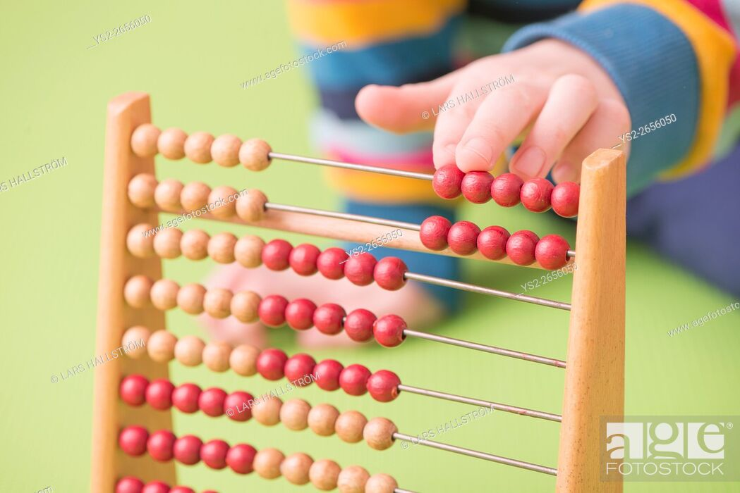 Stock Photo: Child hand counting on abacus. Concept of childhood learning, mathematics and early education.