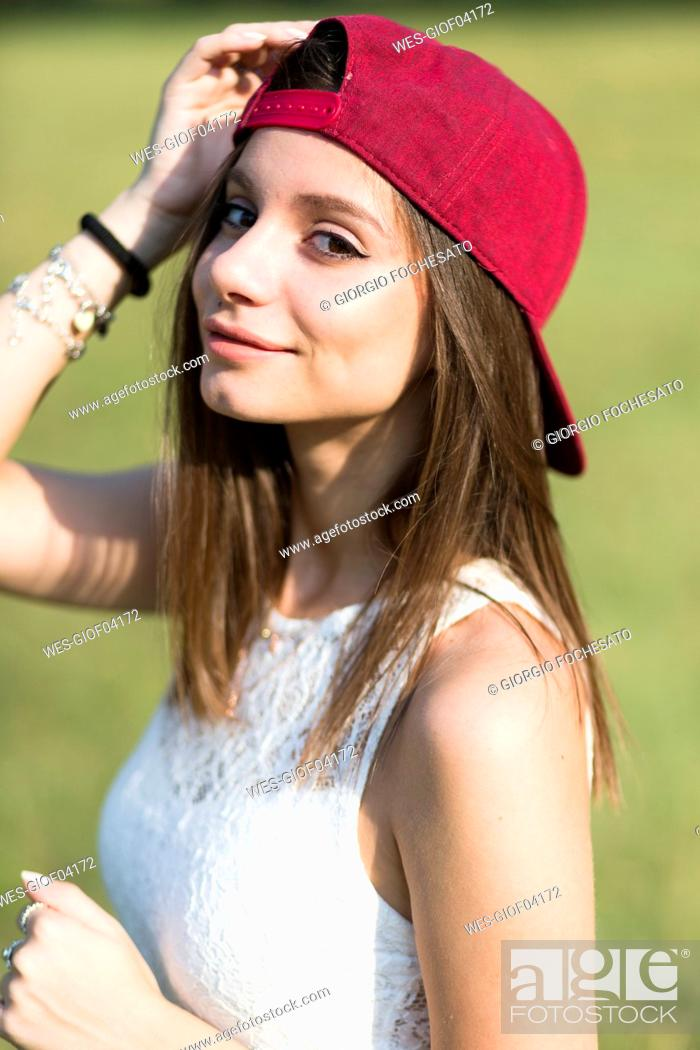 Stock Photo: Portrait of smiling young woman wearing baseball cap outdoors.