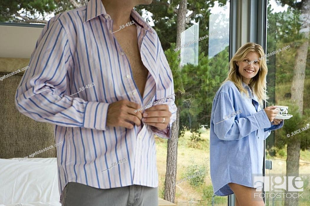 Stock Photo: Couple relaxing in bedroom, woman in man's shirt drinking cup of tea, man getting dressed, smiling.