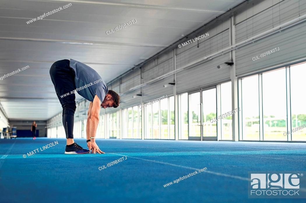 Stock Photo: Runner stretching on indoor running track.