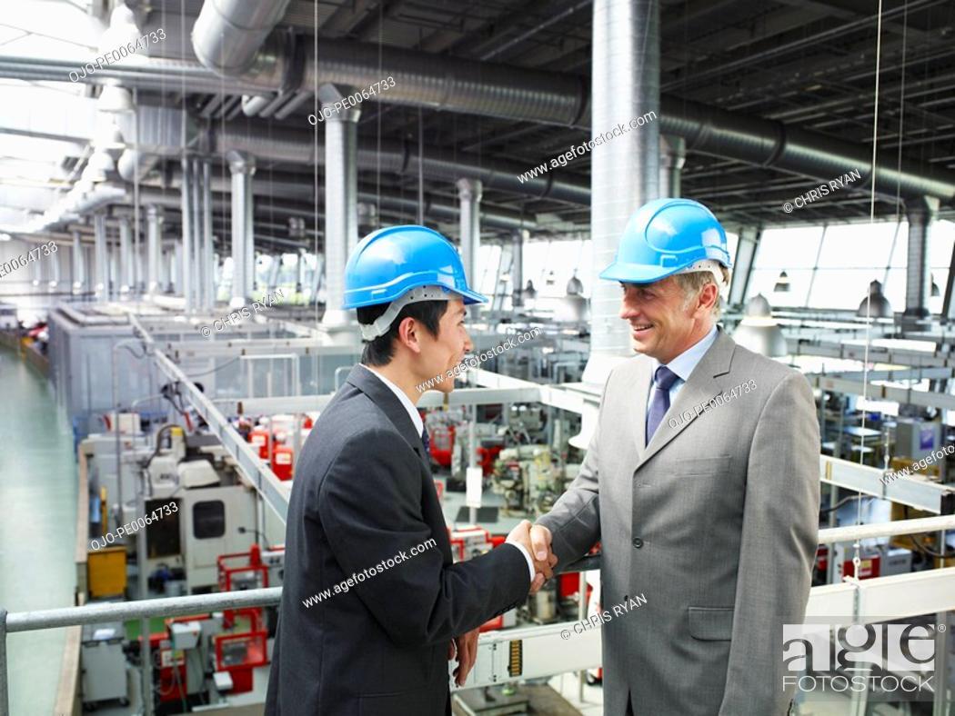 Stock Photo: Businessmen in hard-hats shaking hands.