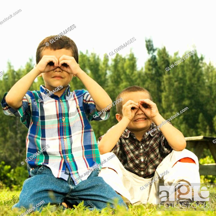 Stock Photo: Close-up of two boys looking through their hands.