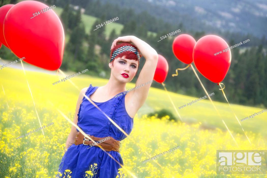 Stock Photo: A beautiful young caucasian female in a canola field with balloons near Spokane, Washington, USA.