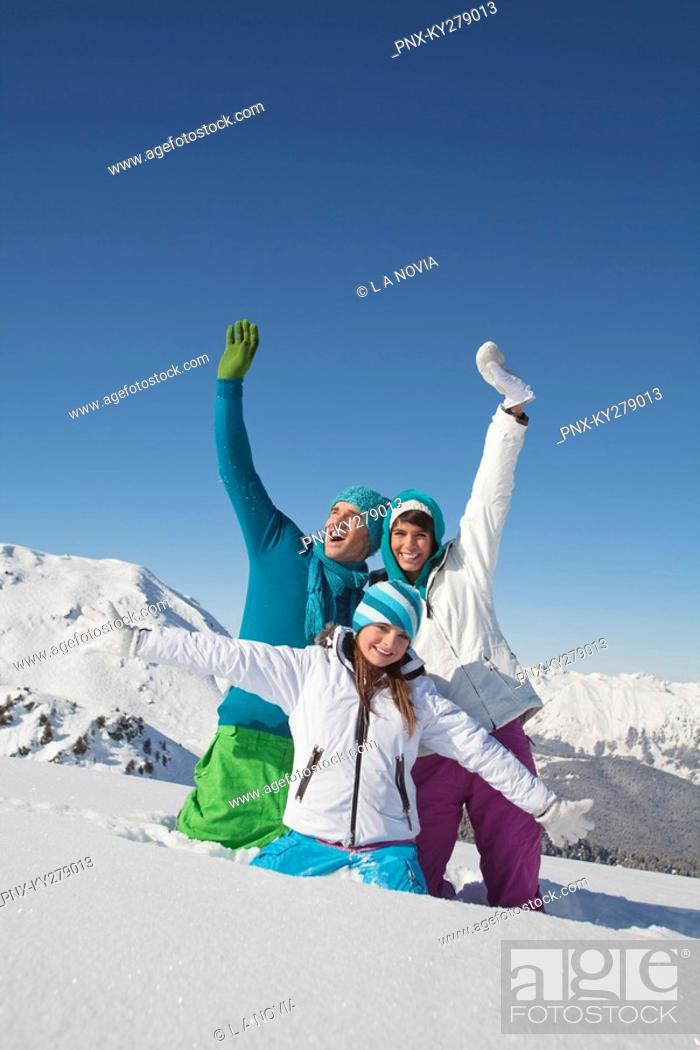 Stock Photo: Couple and daughter in ski wear, playing in snow.