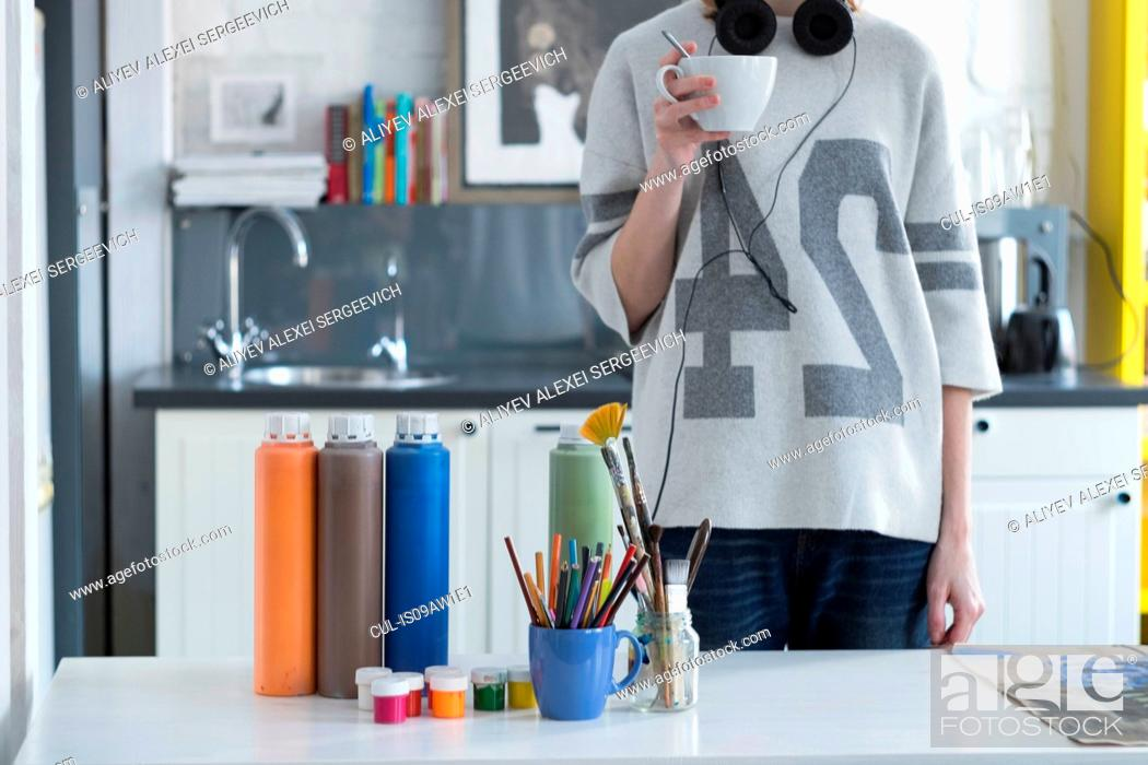 Imagen: Female artist drinking coffee at kitchen table.