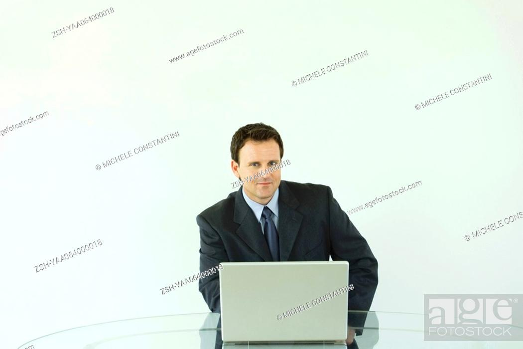 Stock Photo: Businessman sitting at desk, using laptop computer, smiling at camera.