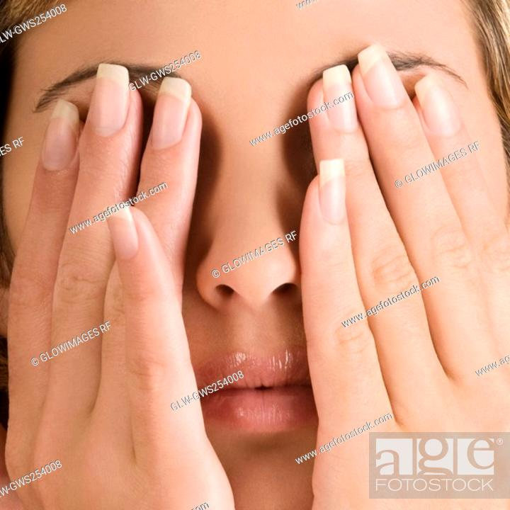 Stock Photo: Close-up of a young woman covering her eyes with her hands.