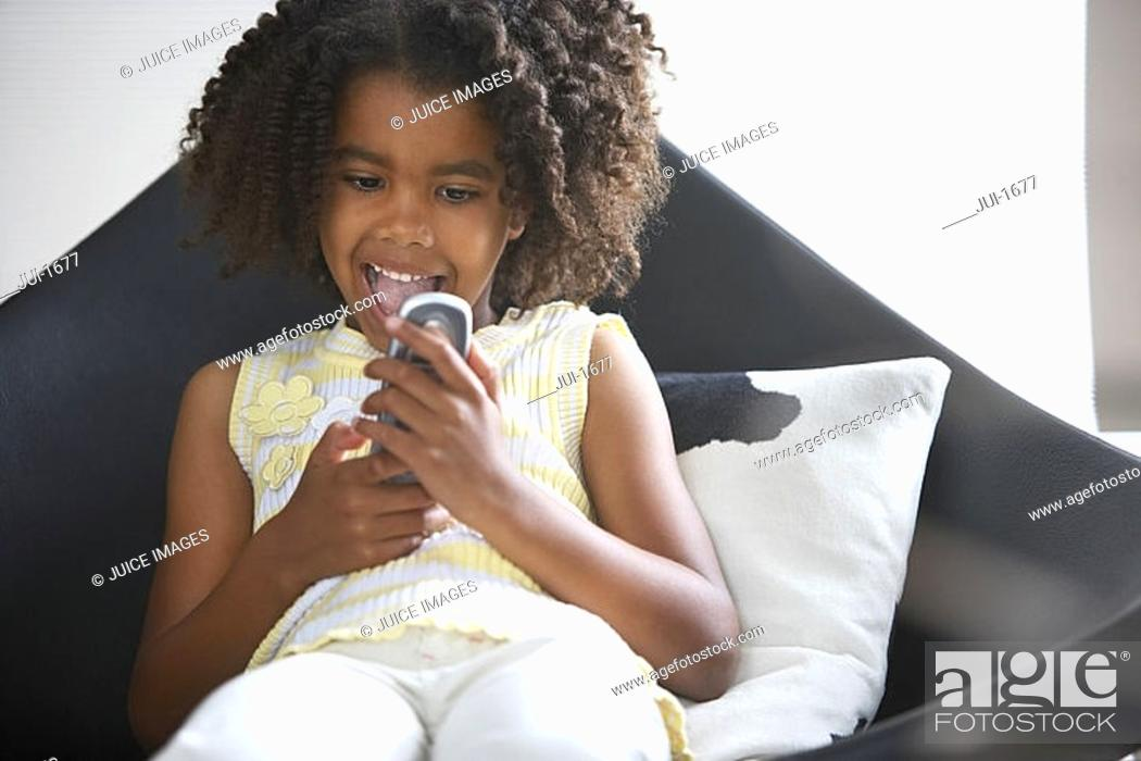 Stock Photo: Girl 8-10 sitting in chair at home, reading text message on mobile phone, mouth open, front view.