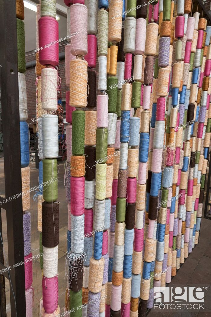 Imagen: Vertical columns of vibrantly coloured thread standing sentinel like an architectural installation in traditional jacquard texile industry.