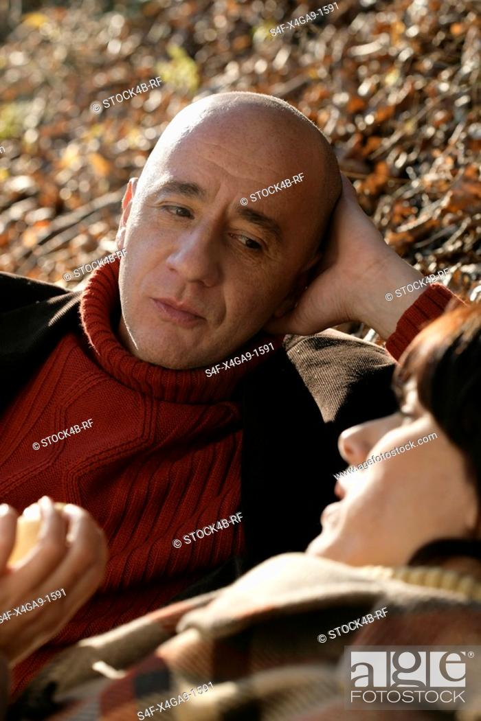 Stock Photo: Mature couple lying on leaves and talking.