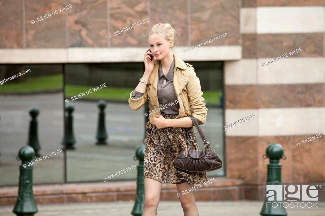 Stock Photo: Businesswoman crossing the road while talking on a mobile phone.
