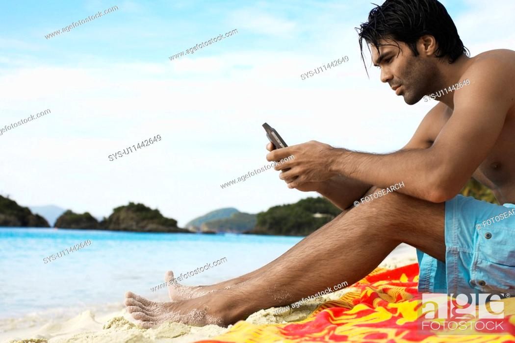 Stock Photo: Young man using mobile phone on beach low angle view, St. John, US Virgin Islands, USA.