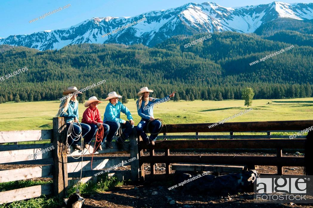 Stock Photo: Cowboys and cowgirls on fence, looking away, Enterprise, Oregon, United States, North America.