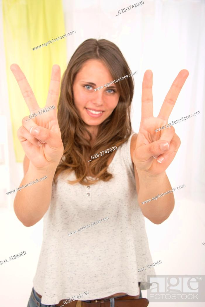 Stock Photo: Young woman making the V of victory with her fingers to express her happiness and her success.
